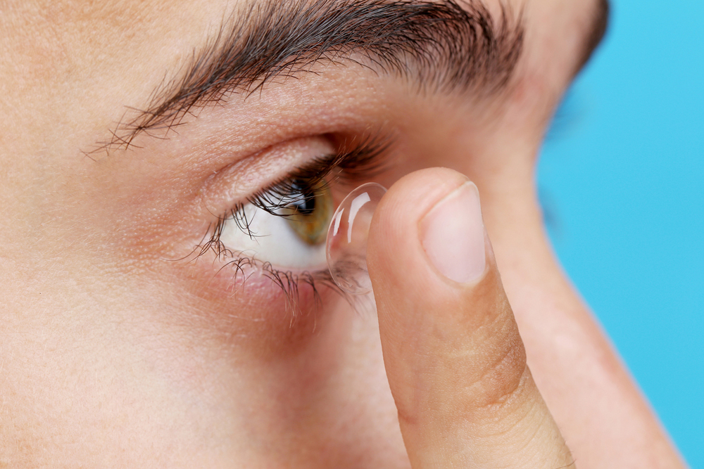Man putting on contact lenses